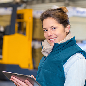Happy woman carrying out a forklift inspection on a tbalet in a warehouse
