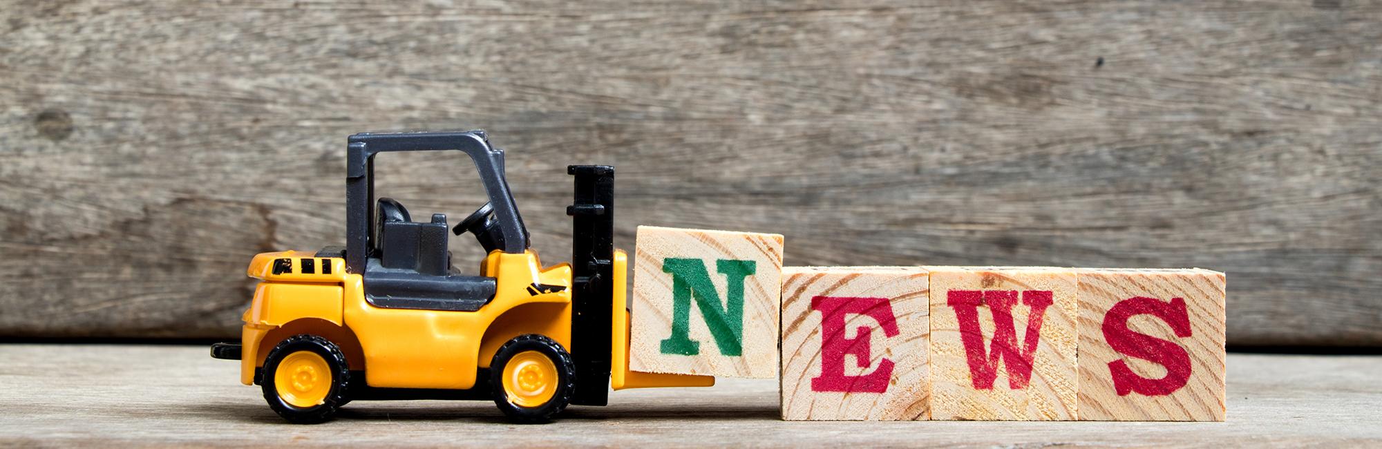 Forklift carrying blocks spelling 'news'