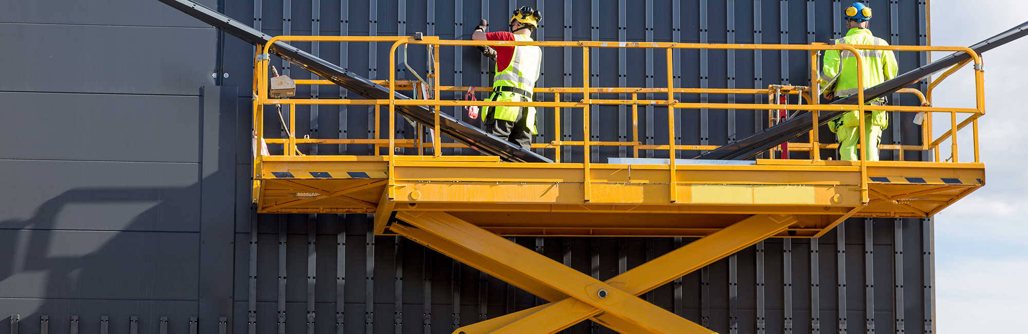Men on access platform working on building
