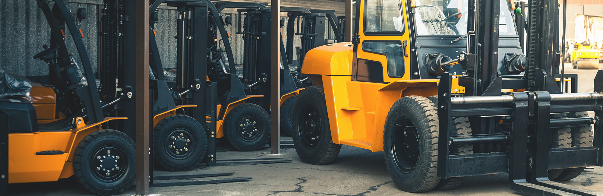 Yellow forklift trucks lined up in a yard with heavy handler in front