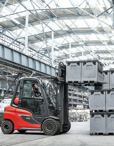 Linde forklift truck lifting grey pallets and stacking them