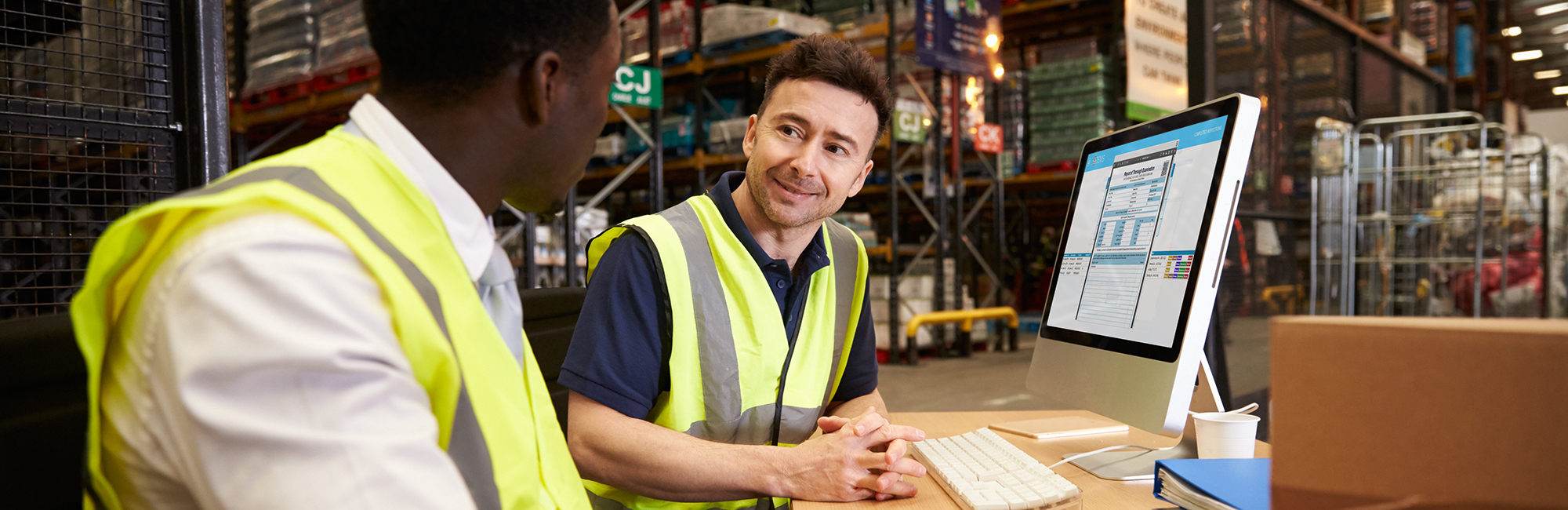Two men looking sat at warehouse desk looking at report